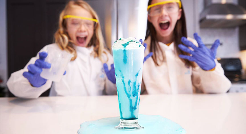 2 girls in a Mad Science lab coats,safety gloves and safety goggles making a home made milk shake that is overflowing on the